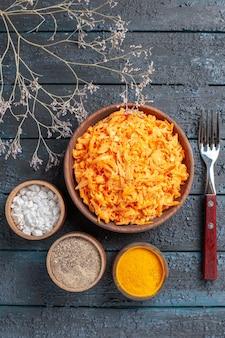 Vista de cima salada de cenoura ralada com alho e temperos na mesa rústica azul-escura salada de cor de saúde salada de vegetais maduros