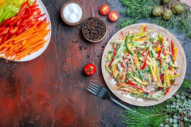 Vista de cima salada de vegetais no prato garfo sal e pimenta preta pimentões cortados coloridos tomates na mesa vermelha escura