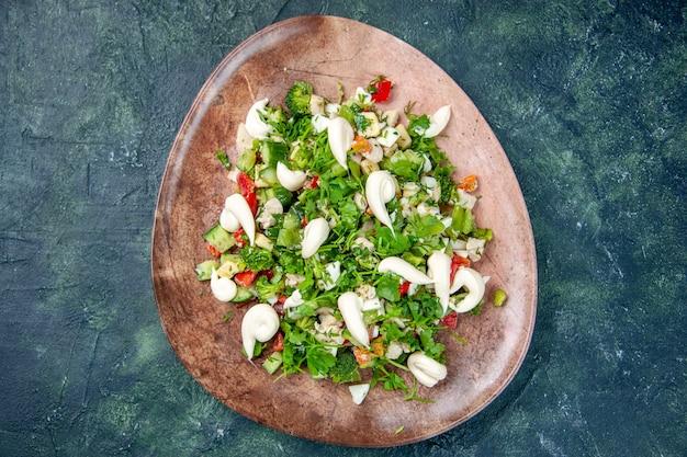 Vista de cima salada de verduras vegetais dentro de prato elegante em fundo azul escuro cor dieta refeição cozinha restaurante comida saúde almoço