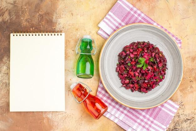 Vista de cima, salada orgânica deliciosa com excelentes garrafas de óleo vermelho e verde e livro de receitas
