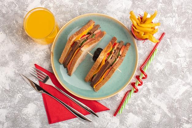 Vista de cima sanduíches saborosos torradas com presunto de queijo dentro de prato azul com suco de batata frita no fundo branco