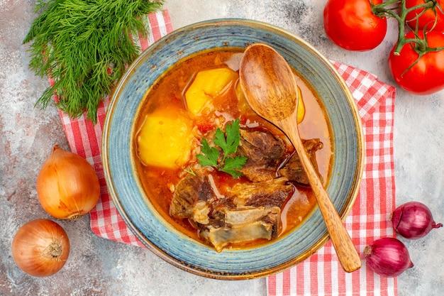 Vista de cima sopa bozbash caseira, colher de pau, toalha de cozinha, um monte de cebolas de tomate endro em fundo nu