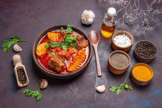 Vista de cima, sopa saborosa com molho de carne com diferentes temperos em um prato de sopa com molho de chão preto