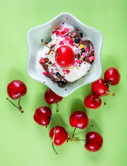 Vista de cima sorvete com chocolate e cerejas em verde claro