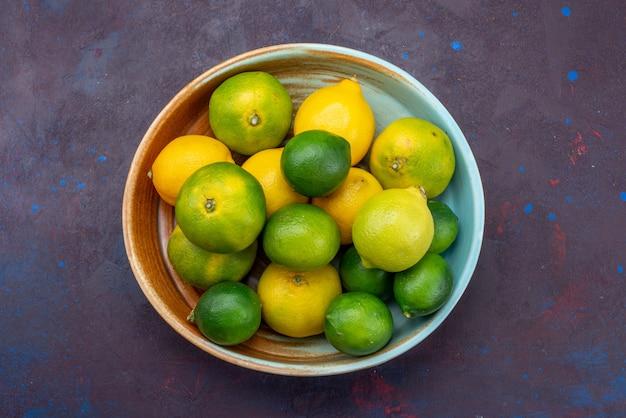 Vista de cima, suculentos limões cítricos e tangerinas na mesa escura, frutas cítricas tropicais exóticas de laranja