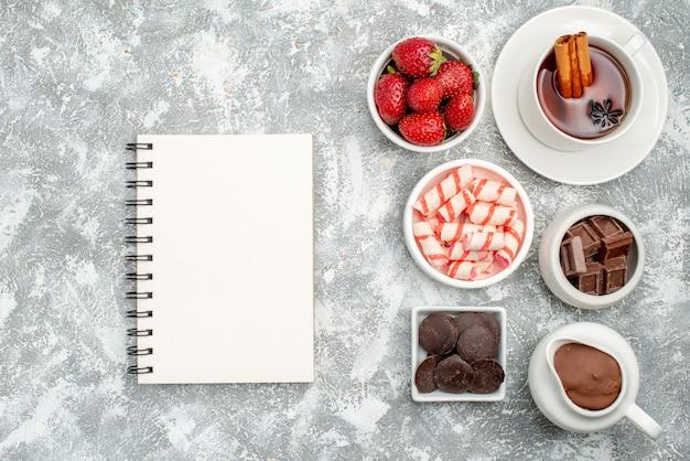 Vista de cima taças com bombons de cacau, morangos, chocolates, chá com canela e um caderno na mesa cinza-esbranquiçada com espaço livre