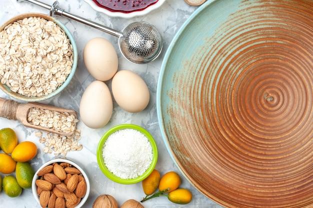 Vista de cima taças de prato redondo com aveia, amêndoas, ovos, geleia e colher de pau