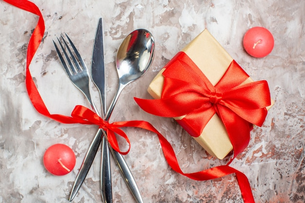 Vista de cima, talheres de prata, colher, garfo e faca com laço vermelho e presentes em uma superfície leve