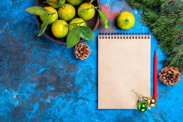 Vista de cima tangerinas amarelas com folhas em uma tigela de madeira, um caderno, lápis vermelho, enfeites de natal na superfície azul