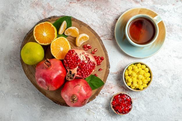 Vista de cima tangerinas e romãs frutas frescas maduras no chão branco cor da árvore frutífera saúde fresco
