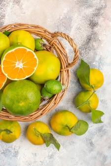 Vista de cima tangerinas frescas em uma cesta de vime cercadas por tangerinas em fundo nu