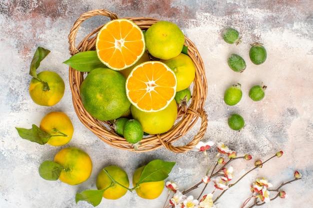 Vista de cima tangerinas frescas em uma cesta de vime cercadas por tangerinas feykhoas em fundo nu