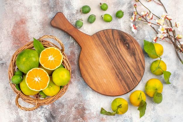 Vista de cima tangerinas frescas em uma cesta de vime e uma tábua de cortar mandarinas feykhoas em fundo nu