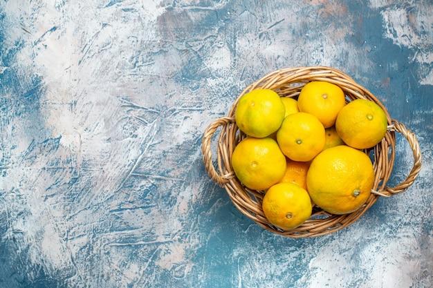 Vista de cima tangerinas frescas em uma cesta de vime em uma superfície branca e azul com espaço livre