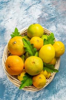 Vista de cima tangerinas frescas em uma cesta de vime na superfície azul e branca