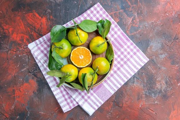 Vista de cima tangerinas frescas em uma tigela na toalha de cozinha em um espaço livre de superfície vermelho escuro