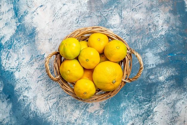 Vista de cima tangerinas frescas na cesta de vime no espaço da cópia da superfície azul e branca