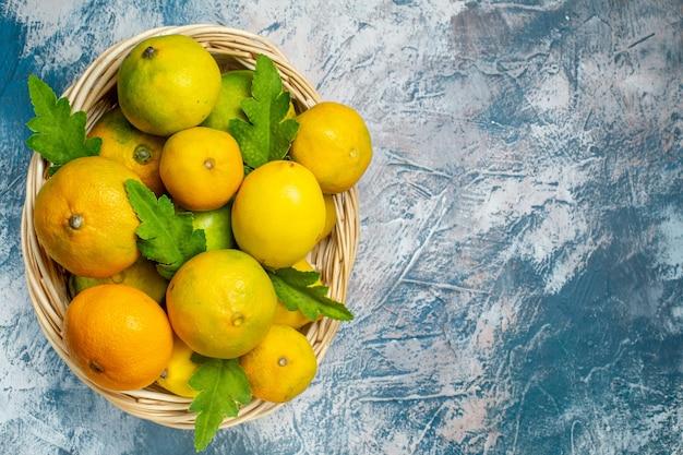 Vista de cima tangerinas frescas na cesta de vime no local da cópia da superfície azul e branca