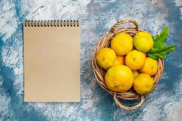 Vista de cima tangerinas frescas na cesta de vime um caderno na superfície azul e branca