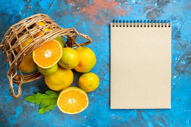 Vista de cima tangerinas frescas na cesta de vime um caderno na superfície azul