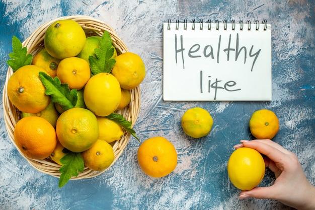 Vista de cima tangerinas frescas na cesta de vime vida saudável escrita no bloco de notas tangerina na mão da mulher na superfície azul e branca