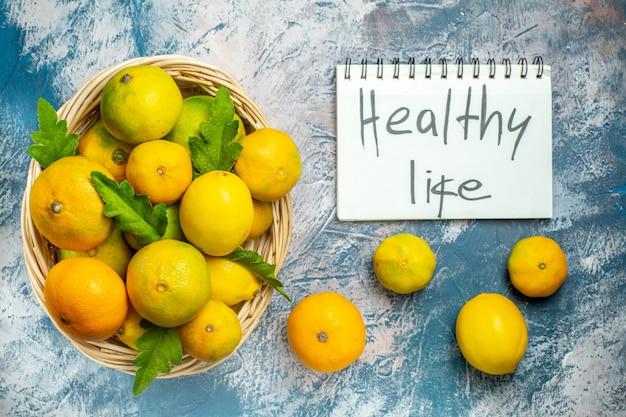 Vista de cima tangerinas frescas na cesta de vime, vida saudável, escritas no bloco de notas na superfície azul e branca