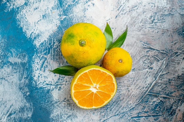 Vista de cima tangerinas frescas na superfície azul e branca