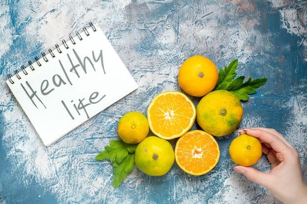 Vista de cima, tangerinas frescas, vida saudável, escritas no bloco de notas, mão feminina, segurando mandarim na superfície azul e branca