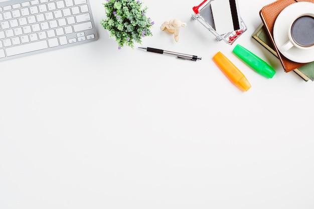 Vista de cima. teclado, caneta, cartão de crédito, caderno e café na mesa de escritório branco