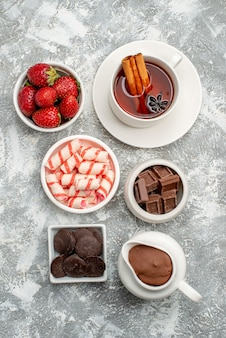Vista de cima tigelas com balas de cacau, morangos, chocolates e chocolates de canela na mesa cinza-esbranquiçada