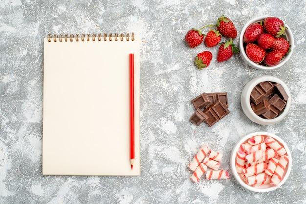 Vista de cima tigelas com bombons de chocolate de morangos e alguns bombons de chocolate de morangos no lado direito e caderno com lápis vermelho no lado esquerdo do fundo branco-acinzentado