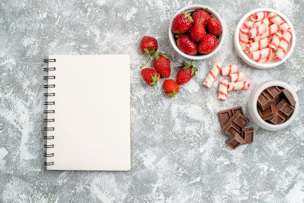 Vista de cima tigelas com chocolates de morango e alguns chocolates de morango no lado direito e um caderno no lado esquerdo da mesa cinza-esbranquiçada