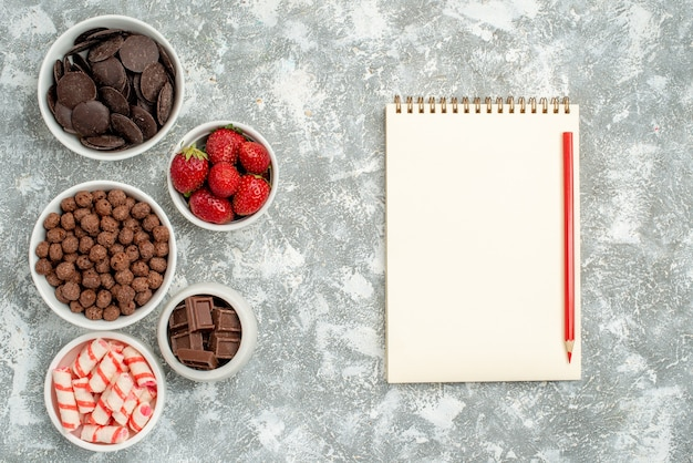 Vista de cima tigelas com doces, morangos, chocolates, cereais e cacau à esquerda e um caderno com lápis vermelho à direita da mesa cinza-esbranquiçada