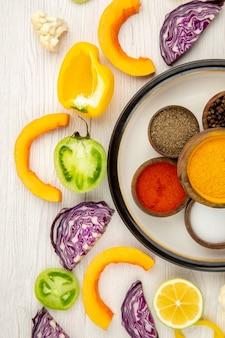 Vista de cima tigelas com especiarias em um prato redondo e vegetais cortados na mesa branca