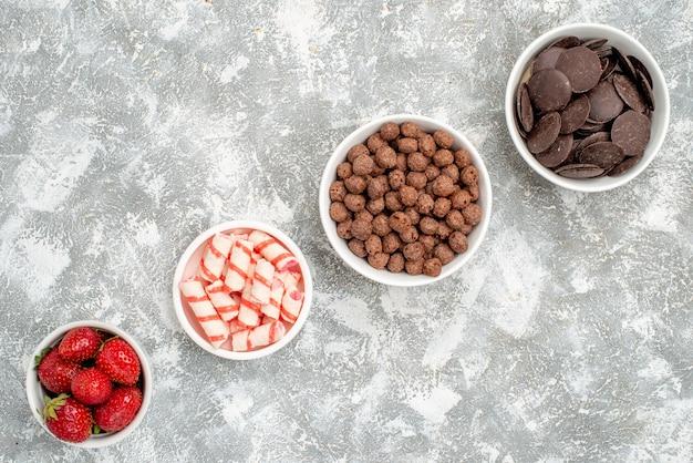 Vista de cima tigelas com filas diagonais com doces de morangos e chocolates de cereais no fundo branco-acinzentado