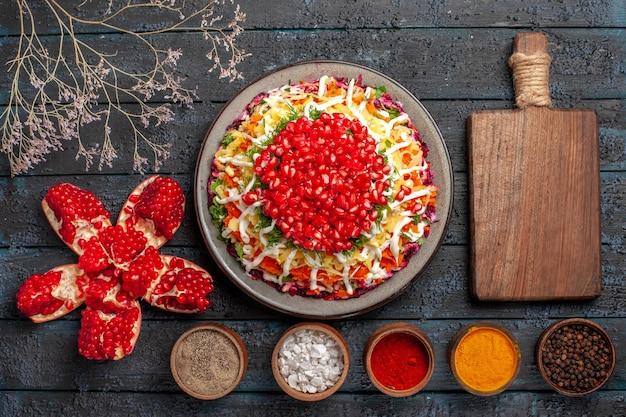 Vista de cima tigelas de comida de natal com especiarias e romã descascadas ao lado da tábua de cortar prato de natal com romã e maionese e galhos de árvores