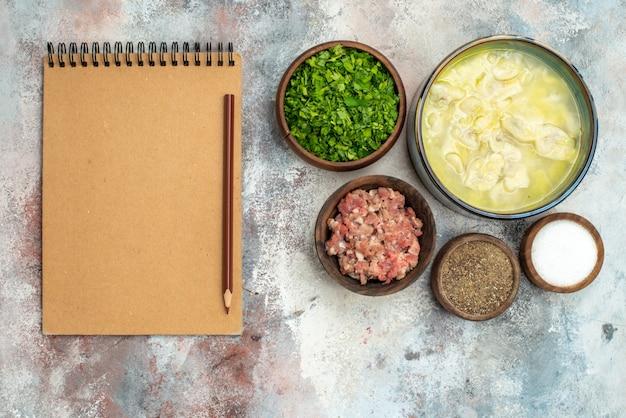 Vista de cima, tigelas dushbara com lápis de carne e especiarias diferentes em um caderno na superfície nua