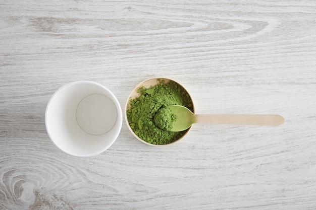 Vista de cima tira o vidro de papel branco e o chá matcha orgânico premium do japão na mesa de madeira, pronto para a preparação do café com leite de maneira moderna. primeira etapa da apresentação. tomando uma colher de chá de pó verde.