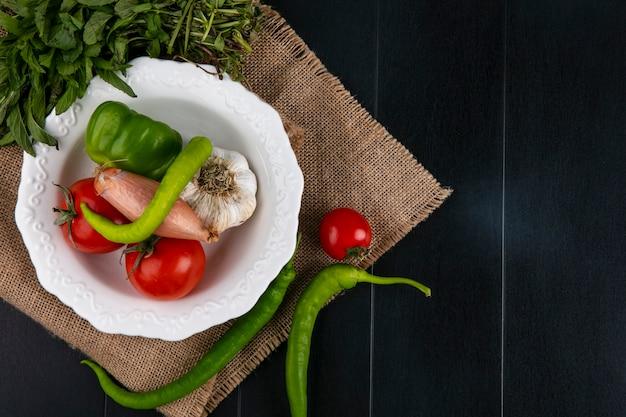 Vista de cima tomate com alho búlgaro e pimenta e cebola em um prato com hortelã em um guardanapo bege