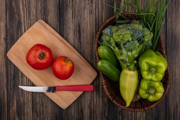 Vista de cima, tomates com uma faca em uma tábua e pepinos, pimentão, brócolis e cebola verde em uma cesta sobre um fundo de madeira