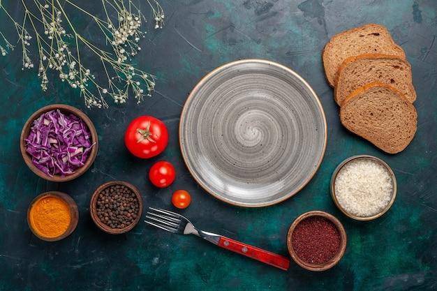 Vista de cima, tomates frescos com temperos e pães em uma mesa azul-escura pão comida prato de vegetais jantar