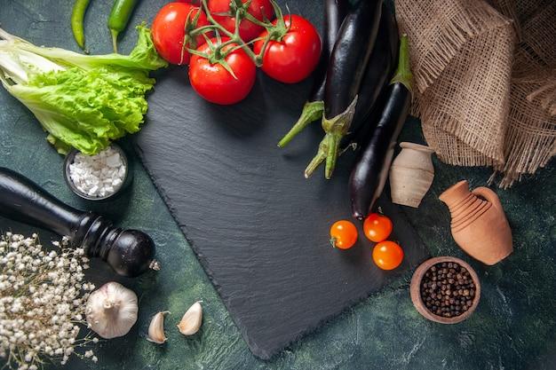 Vista de cima tomates vermelhos frescos com berinjelas na superfície escura jantar salada madura crescer refeição foto alimentos cores