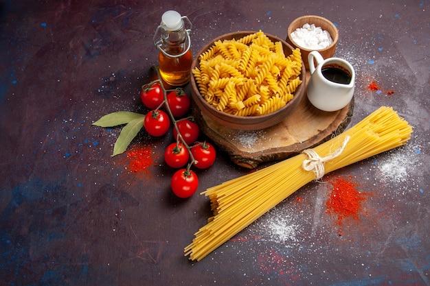 Vista de cima, tomates vermelhos frescos com massa italiana crua na mesa escura