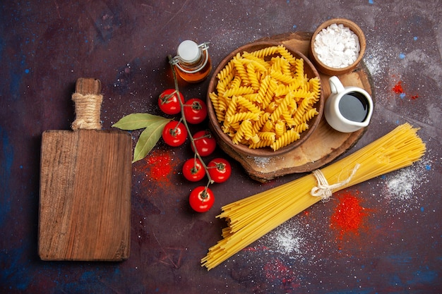 Vista de cima, tomates vermelhos frescos com massa italiana crua na superfície escura comida salada crua refeição de massa