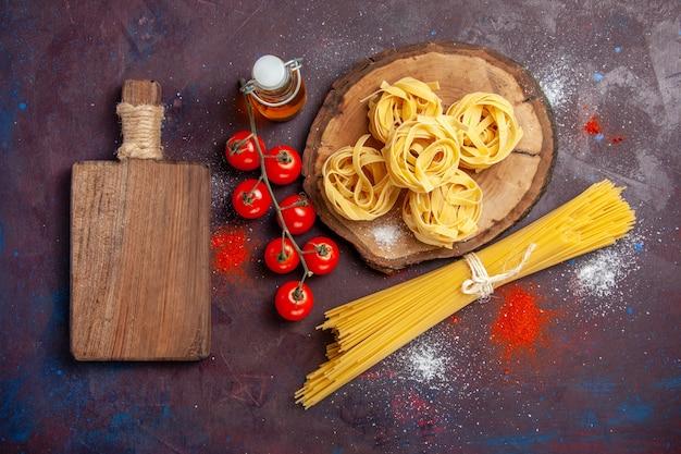 Vista de cima, tomates vermelhos frescos com massa italiana crua no fundo escuro refeição de macarrão com salada crua