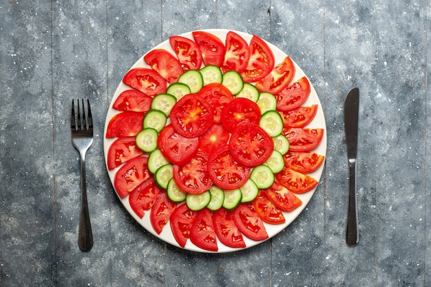 Vista de cima, tomates vermelhos frescos fatiados em fatias de salada na mesa cinza