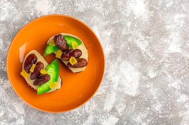 Vista de cima torradas de pão com pepino e ameixas secas dentro de um prato laranja em uma parede branca com pão torrado sanduíche
