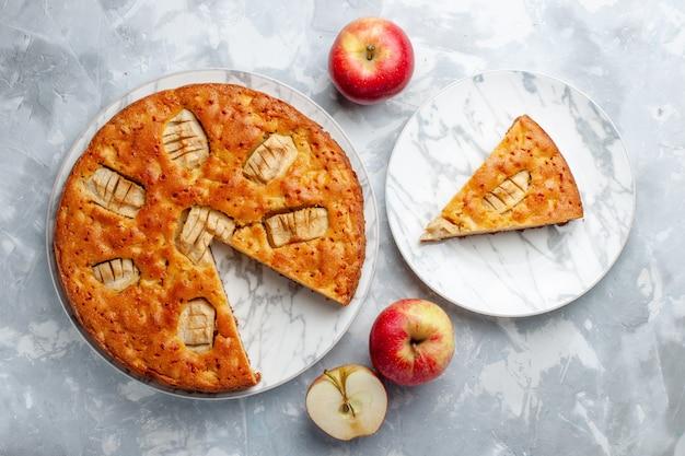 Vista de cima torta de maçã dentro do prato com maçãs no fundo claro bolo de açúcar torta de biscoito