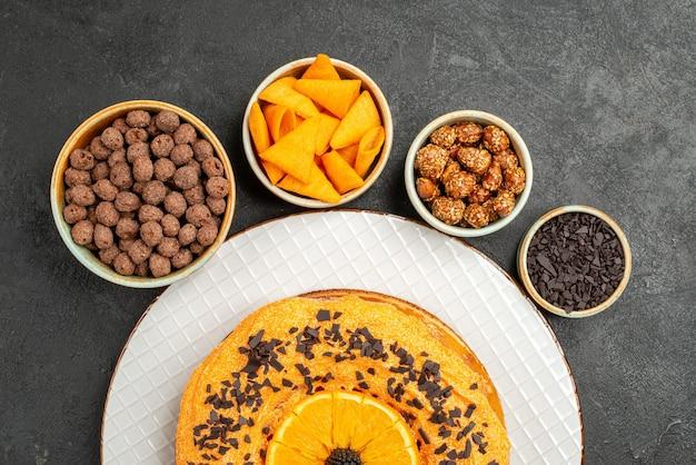 Vista de cima torta doce saborosa com fatias de laranja em biscoito de mesa cinza sobremesa torta doce chá