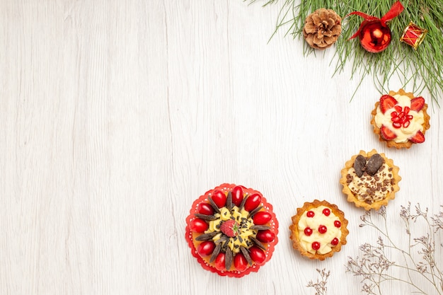 Vista de cima, tortas de bolo de frutas vermelhas e folhas de pinheiro com brinquedos de natal no lado direito da mesa de madeira branca
